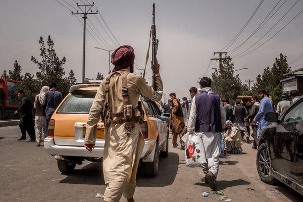 A Taliban member chasing people who were waiting to get to Kabul's international airport on Wednesday.